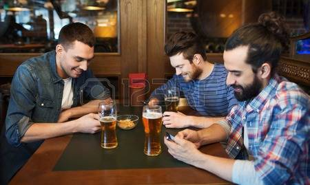 48778511-people-men-leisure-friendship-and-technology-concept-male-friends-with-smartphones-drinking-beer-at